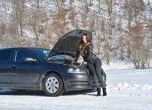 Young fashion woman trying to fix the car. Winter car breakdown - young fashion woman trying to fix the car Stock Images