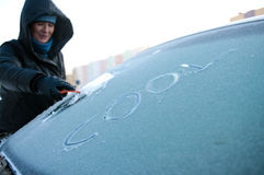 Winter car problem. Woman removing frost off of her car windscreen. Word cool on it Stock Photography