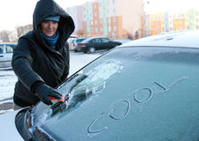Winter car problem. Woman removing frost off of her car windscreen. Word cool on it Royalty Free Stock Images