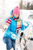 Winter car tire snow chains woman. Winter car tire snow chains young woman have problems Royalty Free Stock Images