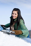 Winter car - woman remove snow from windshield. With snow brush Royalty Free Stock Image