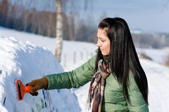 Winter car - woman remove snow from windshield. With ice scraper Stock Images