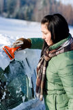 Winter car - woman remove snow from windshield. With ice scraper Royalty Free Stock Photo