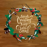 Winter card with berries, cone, fir tree on wooden texture backg. Round. In round frame calligraphic handwritten text Merry Christmas and Happy New Year. Design Royalty Free Stock Photo