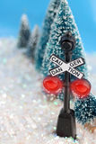 Winter caution. Caution, danger railroad sign glowing with red lights in a winter wonderland setting Royalty Free Stock Photo