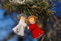 Winter celebrations beautiful background. Two small dolls angels with sprig of pine sprinkled with snow. winter celebrations beautiful background Stock Photos