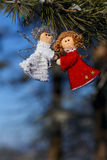 Winter celebrations beautiful background. Two small dolls angels with sprig of pine sprinkled with snow. winter celebrations beautiful background Stock Image