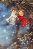 Winter celebrations beautiful background. Two small dolls angels with sprig of pine sprinkled with snow. winter celebrations beautiful background Royalty Free Stock Images