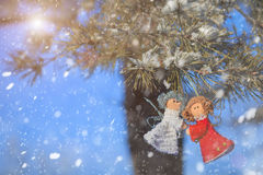 Winter celebrations beautiful background. Two small dolls angels with sprig of pine sprinkled with snow. winter  celebrations beautiful background Royalty Free Stock Photo