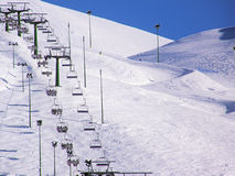 Winter chairlift. A winter chairlift working in a mountain full of snow Royalty Free Stock Image
