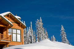 Winter chalet. Log chalet in winter looking out on snow and trees with bright blue sky Royalty Free Stock Images