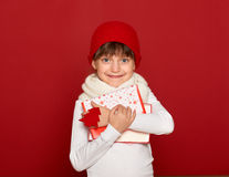 Winter, child,  christmas concept - happy girl in hat with box gift show fir tree wool toy on red Royalty Free Stock Image