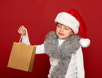 Winter, child,  christmas concept - happy girl in santa hat with box gift on red Stock Photos