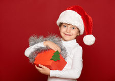 Winter, child,  christmas concept - happy girl in santa hat with box gift show fir tree toy on red Royalty Free Stock Photo