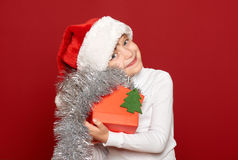 Winter, child,  christmas concept - happy girl in santa hat with box gift show fir tree toy on red Stock Image
