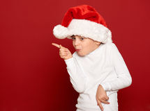 Winter, child,  christmas concept - happy girl in santa hat dancing on red Stock Photography
