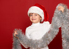 Winter, child,  christmas concept - happy girl in santa hat with decoration on red Royalty Free Stock Photos