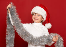 Winter, child,  christmas concept - happy girl in santa hat with decoration on red Royalty Free Stock Image
