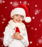 Winter, child,  christmas concept - happy girl in santa hat show Royalty Free Stock Image