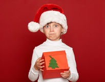 Winter, child,  christmas concept - surprised girl in santa helper hat with box gift on red Stock Photos