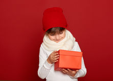 Winter, child,  christmas holiday concept - happy girl in hat with box gift on red Stock Image