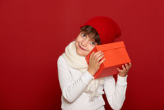 Winter, child,  christmas holiday concept - happy girl in hat with box gift on red Royalty Free Stock Photography