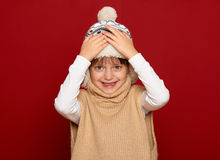Winter child concept - happy girl in hat and sweater on red Royalty Free Stock Photos