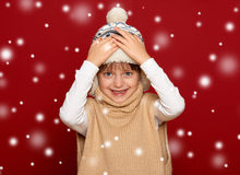 Winter child concept - happy girl in hat and sweater on red Stock Images