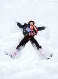 Winter child play lie in snow. At sunny day Stock Photo