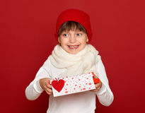 Winter, child,  valentine love concept - happy girl in hat with box gift show heart wool toy on red Stock Photo