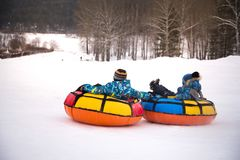 children are rolling down snow tubing royalty free stock photo