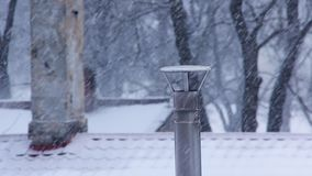 Winter Chimney Smoke in the Snowfall. Smoke Comes From the Chimney. Heavy Snowfall in Winter Frosty Day stock footage