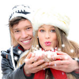 Winter christmas. Happy winter christmas couple blowing greetings wishes with snow flakes Stock Photo