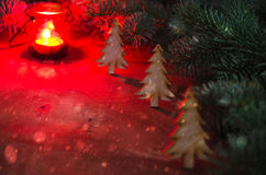 Winter Christmas Backgroun. Christmas Tree. Burning red candle. Snow Falling Effect. Dark image. Stock Photos