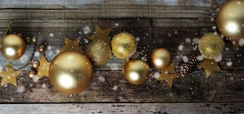 Winter christmas background. Gold baubles decorations, over old wooden plank. Top view. Banner royalty free stock images
