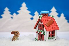 Winter Christmas card with a Bunny near the house. Beautiful Christmas winter card with a Bunny and a house with a red roof near the snowy forest from the trees Stock Photo