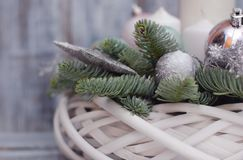 Winter or Christmas centerpiece wreath with candles, new year toys, spice and fir branches on gray wooden background royalty free stock images