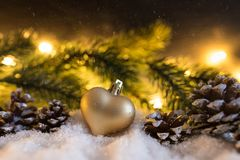 Winter christmas decoration with heart shaped christmas ornament, cones, fir branch and glowing lights. Snowy winter christmas decoration with heart shaped Stock Images