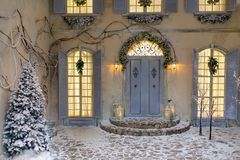 Winter christmas decoration. House decorated for Christmas outside, courtyard. Vintage street interior with tree, door and lights in windows. Winter christmas stock images