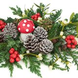 Winter and Christmas Decorative Display. With fly agaric mushroom, holly, ivy, mistletoe, cedar and juniper leaf sprigs and pine cones on white background Royalty Free Stock Photos