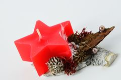 Winter christmas handmade decoration, red star shaped candle on wooden stand with cones and beads Stock Images