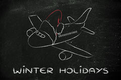 Winter and Christmas holiday: plane with santa claus hat. Airplane with santa claus hat: concept of Christmas and winter holidays Royalty Free Stock Photography