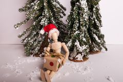 Winter Christmas holiday scene wooden jointed doll wearing Santa hat holding present. Cold winter Christmas holiday scene wooden jointed maniquin doll wearing stock photo