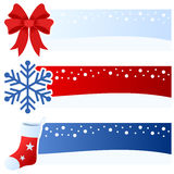 Winter or Christmas Horizontal Banners. A collection of three wintertime or Christmas horizontal banners with a red bow, a snowflake and a hanging sock on blue Royalty Free Stock Photography