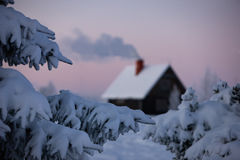 Winter Christmas landscape with smoke from the chimney house Royalty Free Stock Image