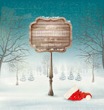 Winter christmas landscape with a wooden ornate sign and a santa Royalty Free Stock Image
