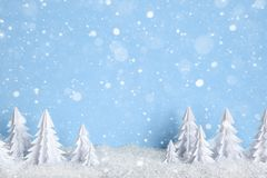 Winter Christmas minimalist background with white paper trees on blue  drawing snowflakes Stock Photo
