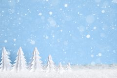 Winter Christmas minimalist background with white paper trees on blue drawing snowflakes Stock Photography