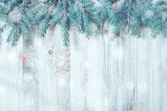 Winter Christmas and New year background. Blue fir tree branches with winter snowflakes on the wooden background royalty free stock photos