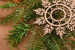 Wood snowflake on pine branch on beige background Royalty Free Stock Photography